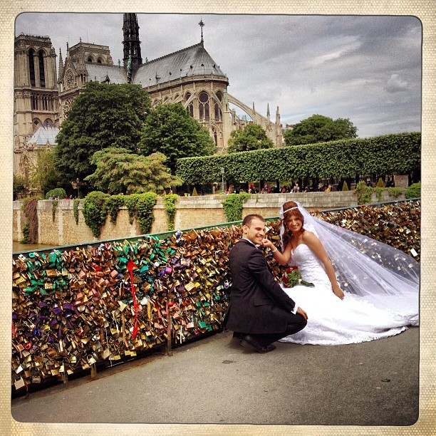 Newlyweds installing their love locks on the bridge behind the Notre Dame.